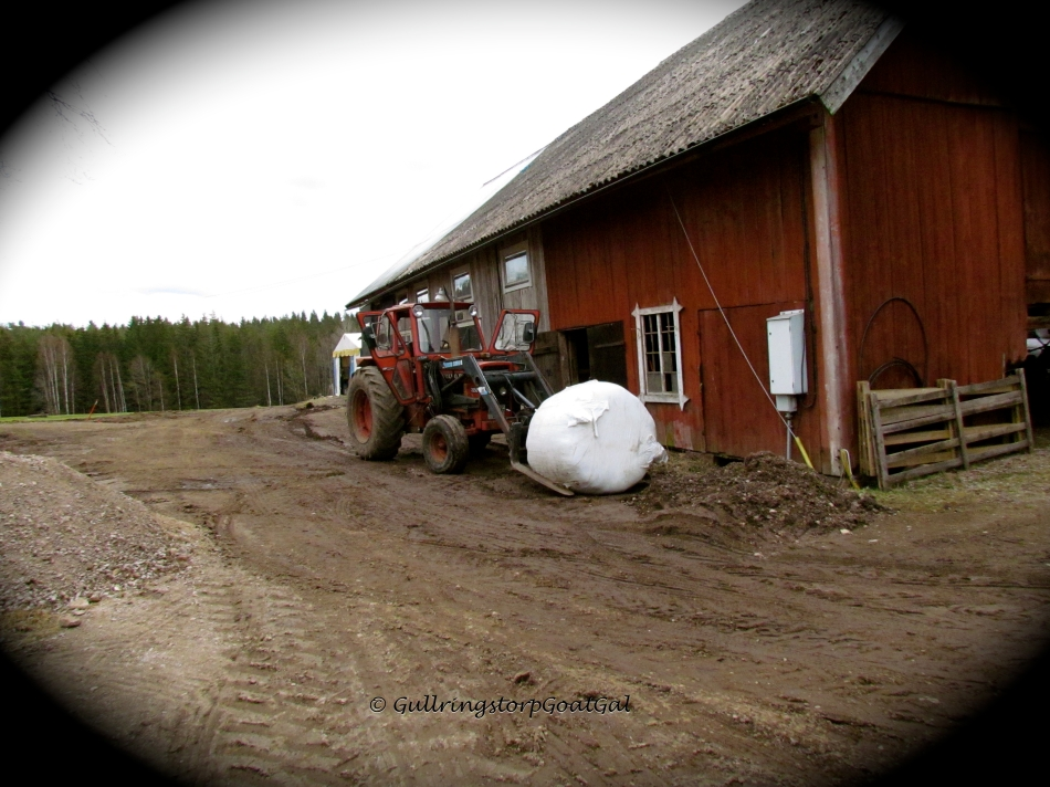The farmer picks up the first bale with his tractor