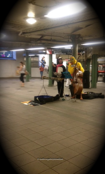 Street musicians performing in costume on the subway platform